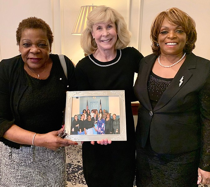 District Court Judge Becky Moore, center, is presented a photo by General District Court clerks Marion Jackson and Hope Mayfield at Moore's retirement luncheon Jan. 31 at Belle Haven Country Club.