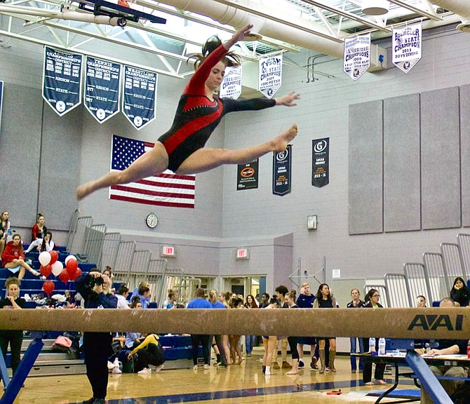 Gymnast Kerry Gallagher of Herndon High School performs a split leap on beam at Chantilly High School.
