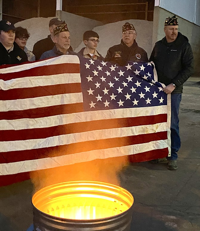 Members of The Wayne M. Kidwell American Legion Post 184 Herndon-Reston and Scouts of Troop 1570 of the National Capital Area Council, Powhatan District in Herndon, unwrap an unserviceable and worn casket flag, preparing it for retirement by burning.