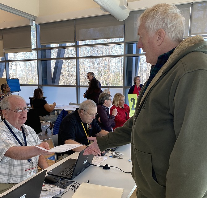 On Feb. 22, 2020, Charlie Quinn, a Fairfax County Elections Officer at the North County Absentee Satellite office in Reston, hands a paper to Rob Loesch of Reston, an in-person absentee voter.