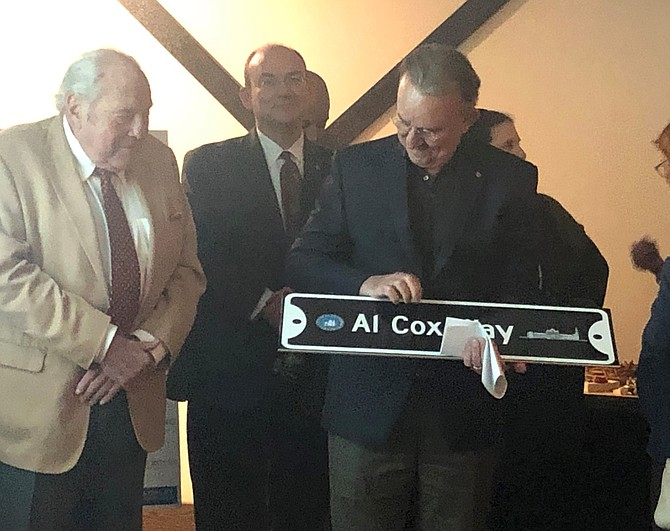 Al Cox holds a sign with his name at a Feb. 7 farewell reception at the Old Dominion Boat Club celebrating his 28 years of service as the city's Historic Preservation Manager. Cox will retire Feb. 28.