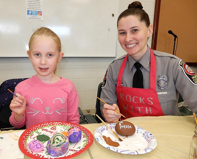 Laila Eimers, 5, paints cheerful designs while Police Officer J. Renfrow turns her rock into a potato.