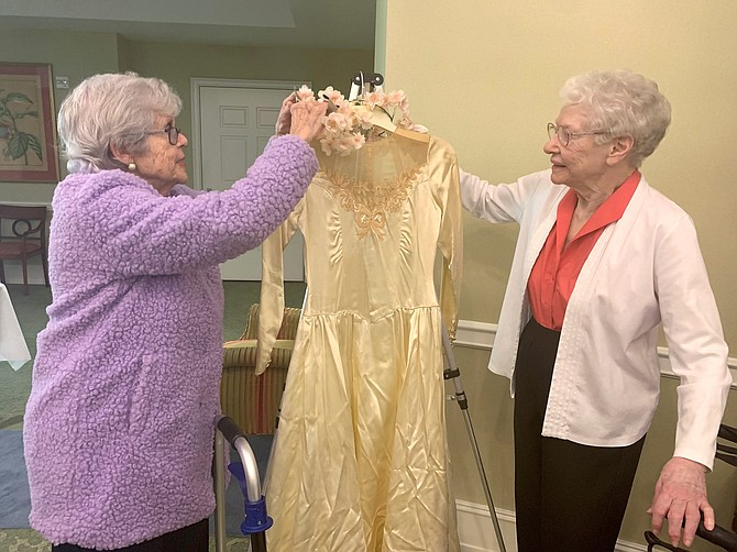 Nancy Gamble and Betsy Ramirez of Goodwin House Alexandria adjust the neckline of the 1940s wedding dress featured at the Feb. 14 Lasting Love Wedding Expo display of wedding gowns and photographs.