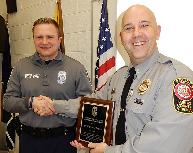 Lt. Josh Laitinen (on right) presents the 2019 Officer of the Year award to PFC Kory Pfeiffer.
