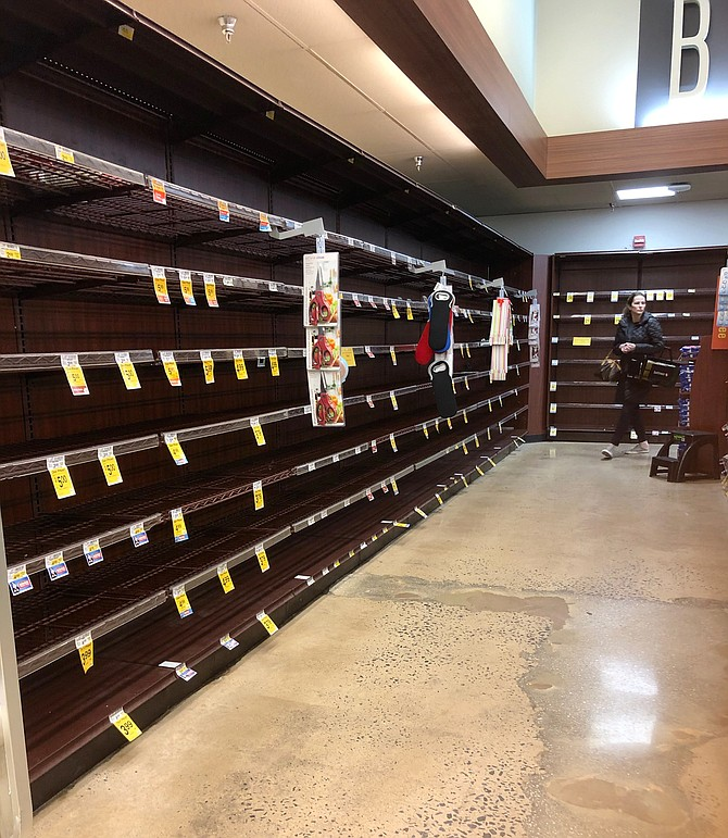 A woman turns the corner at the Great Falls Safeway into an aisle that is typically stocked with bread.