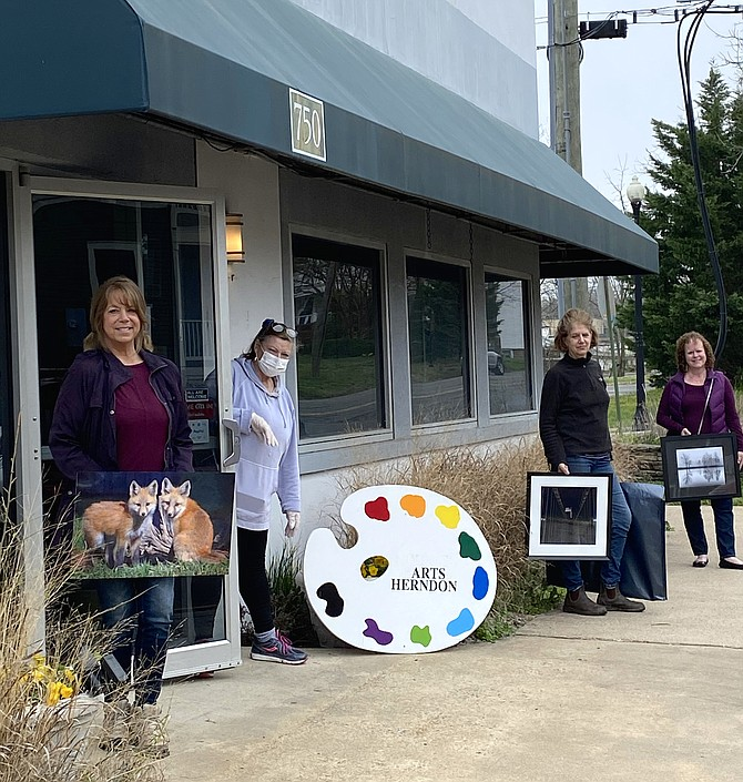 Finalists in the 11th Annual Photography Exhibit pick up their works after Arts Herndon cancels the Exhibit and Reception due to COVID-19. From left on sidewalk: Photographers Suzanne Stout of Potomac Falls, Sarah Strickler of Arlington and Janet Sifers of Oak Hill. Masked, President & CEO of Arts Herndon, Jo Ormesher, holds the door open.