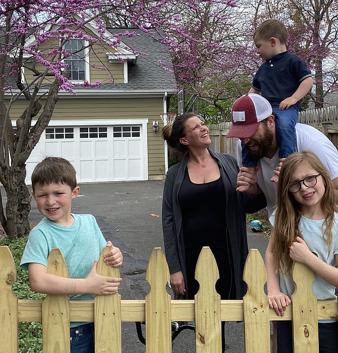 The Spear family of the Town of Herndon, Jay, 5, mom Christin, dad Mike, Zach, 2, and Lily, 5, stay behind the new driveway fence Mike installed. On the other side, a 6-foot social distancing chalk line keeps others a safe COVID-distance away from the family.