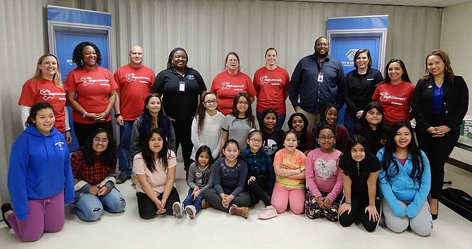 The Raytheon employees, Boys & Girls Club leaders and local children gather for a group photo at the event's end.