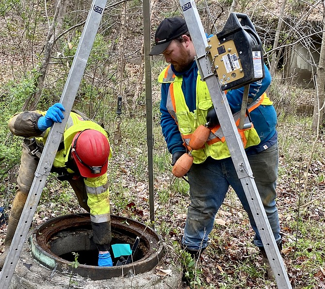Matthew Moss, of Pennsylvania, and Tom Thompson, of Ohio, lower robot into wastewater pipeline in the Pohick Stream Valley area.