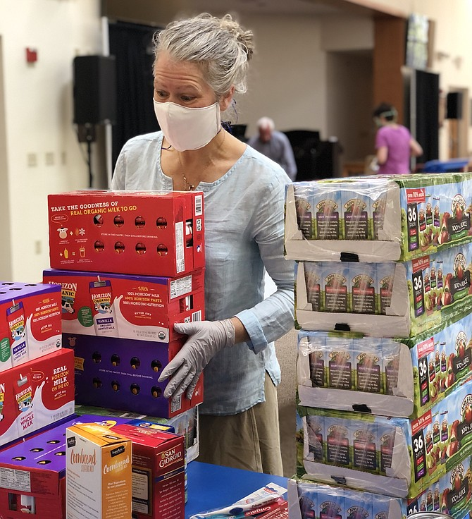 During the COVID-19 crisis, volunteer pantry co-leader, Amy Shaw, readies donations at Good Shepherd Lutheran Church in Herndon for distribution by the South Lakes High School Parent Teacher Student Association Food Pantry.
