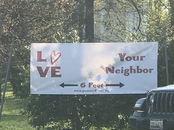A sign at Potomac United Methodist Church encourages loving your neighbor from a distance.
