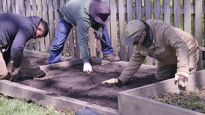 Tom Hayes, right, and two workers prepare garden beds for vegetables.