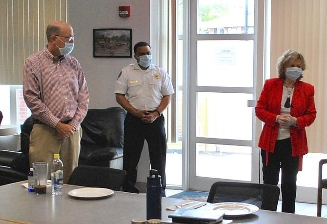 Alexandria Fire Chief Corey Smedley, center, listens as Friendship Veterans Fire Engine Association board member Marion Moon, right, kicks off the organization's Feed the Fire/EMS meals program April 21 at AFD headquarters. Moon, along with former city councilman Frank Fannon, left, are sponsoring the initial three weekly meals for firefighters and EMS personnel.