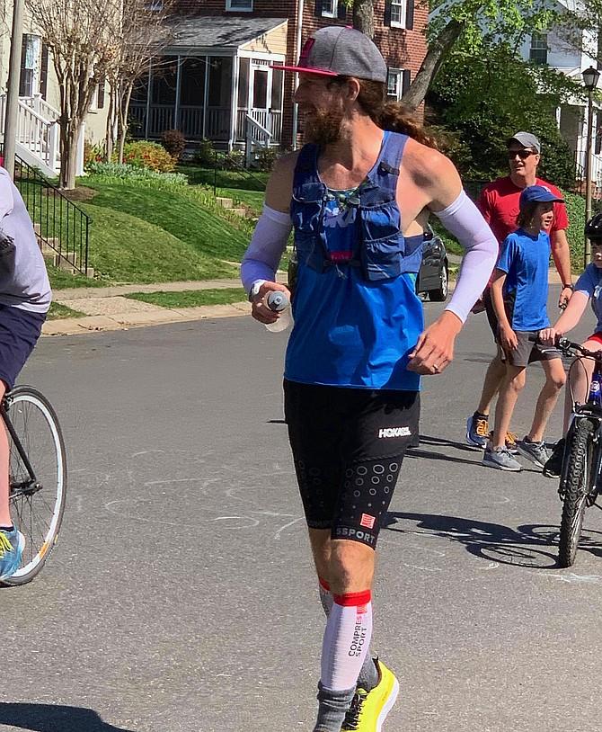 Michael Wardian, 46, running with the kids in his Arlington neighborhood cheering, on his way to winning the first ever Quarantine Backyard Ultramarathon.