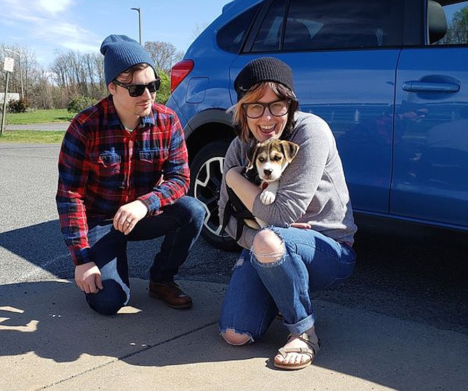 A new puppy, adopted virtually from the Animal Welfare League of Alexandria, makes the day of a couple.