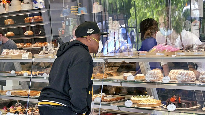 A Randolph's customer stares through the new plexiglass barriers as he selects his cupcakes for Mother's Day.