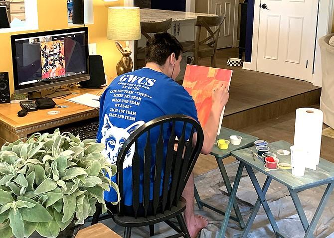 Gabe Kimmel, Senior from Fairfax, working on his self-portrait, inspired by artist Jean-Michel Basquiat.