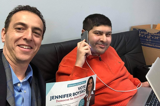 After suffering a knee and spine injury, Toora Arsala still shows up to make phone calls for a candidate. Here, he is pictured with Del. Marcus Simon (D-53).