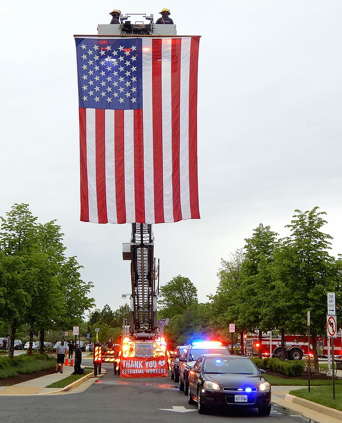 Fairfax City Fire Station 3's tower ladder truck displays a huge American flag to honor the staff of Inova Fair Oaks Hospital.