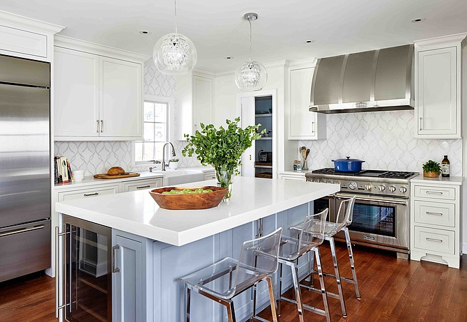 The sunlit and airy kitchen by Winn Design + Build includes a Claridges Thassos Water Jet tile backsplash and pendant lighting by Shades of Light.
