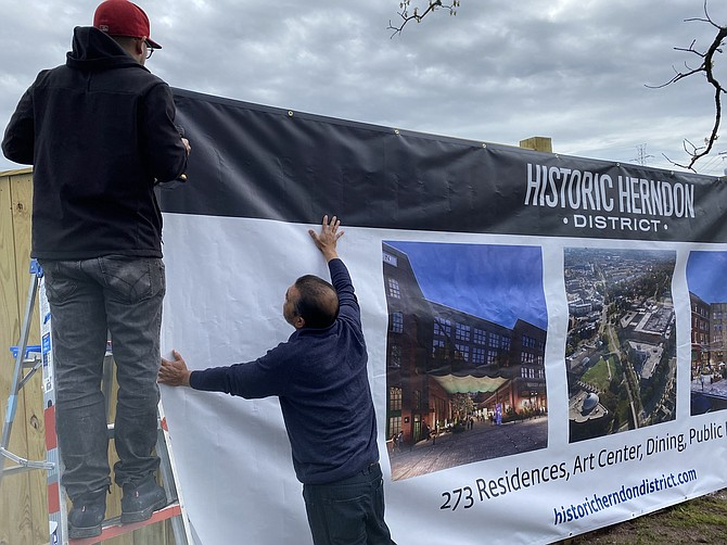 Israel Diaz, Jr. and Israel Diaz, Sr. install the graphic banner announcing 'Building Excitement' for Comstock's Herndon Downtown Redevelopment Project.