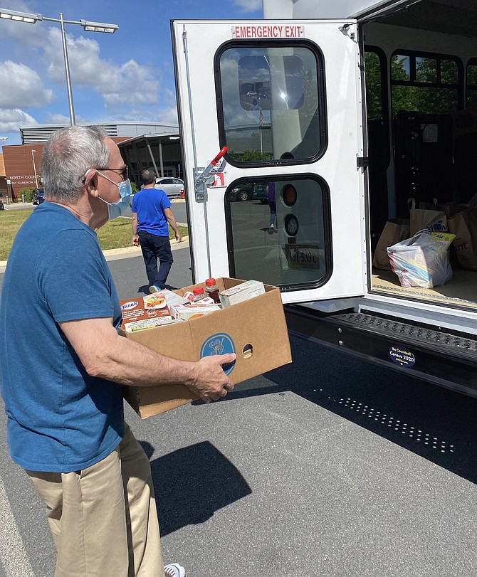 Here comes Jay Hadlock with another box of food to load up for Stuff the Bus, held at the North County Government Center in Reston.