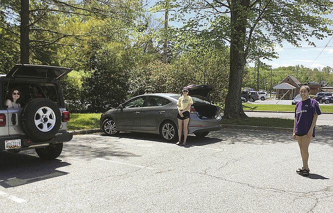 "Sophie Shapiro, in the back of her car, Maya Rosenberg, standing next to hers, and Sheerin Naimi, right, enjoy a ""social distancing"" visit in the Potomac Library parking lot Saturday."