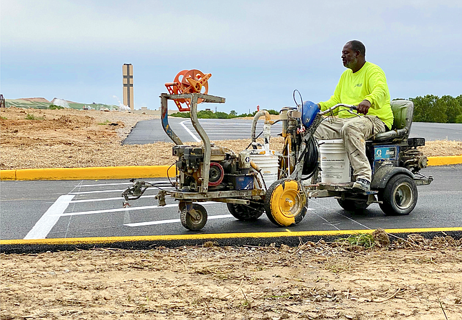 "Using equipment akin to vehicles from ""Mad Max: Fury Road,"" workers paint lines at new Laurel Hill Park parking lot in preparation of site opening."