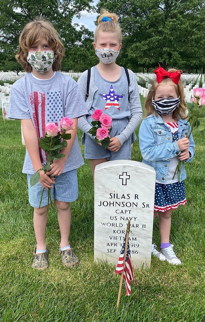 Wearing protective masks, siblings Rory, 8, Sarah, 9, and Norah, 6, Mogle visit the grave of their great-grandfather, Silas Johnson, May 25 at Arlington National Cemetery. Johnson was a Naval Aviator and served in World War II, Korea and Vietnam. His wife, Lucille, is buried with him.