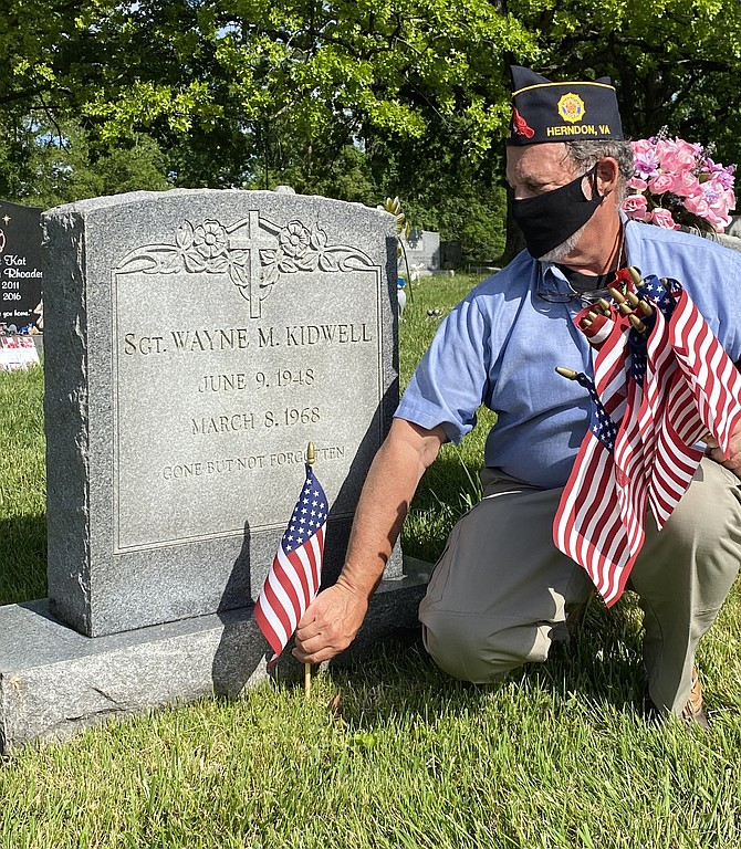 At Chestnut Grove Cemetery in the Town of Herndon for Memorial Day 2020, Michael Cutler, 2nd Vice Commander of The Wayne M. Kidwell American Legion Post 184 Herndon-Reston, adds a remembrance flag to the final resting place for Sgt. Wayne M. Kidwell, United States Army, killed in action during the Vietnam Conflict.