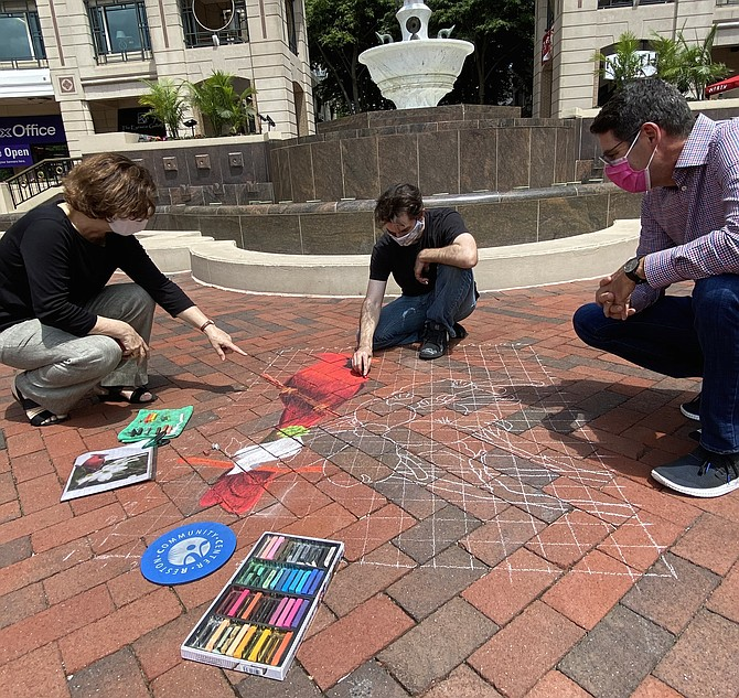 Anne Delaney, Art Reston Executive Director, points out the detail in local artist Ben Morse's chalk art of the Virginia State Bird and Flower, as Morse continues to work and Robert Goudie, Executive Director, Reston Town Center Association, looks on.