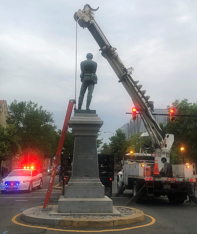 A crane maneuvers into place during the early morning hours of June 2 to begin the removal of the Appomattox Statue at the intersection of Washington and Prince streets.