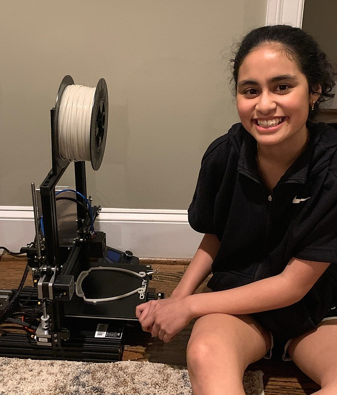 Anisha Talreja of McLean, a TJHSST freshman, poses next to a 3D printing machine the group uses to produce masks.