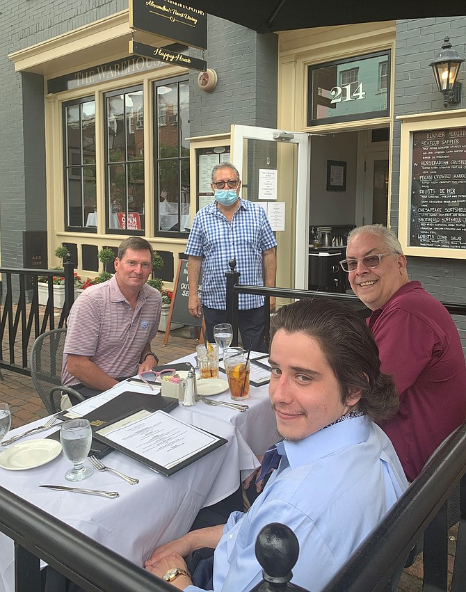Warehouse Restaurant owner Hossein Pishdad, standing, serves a meal to Craig Dyson, John Moorman and Taylor Barnes June 3 in Old Town. Indoor dining will resume beginning June 12 as part of Phase Two of the Virginia Forward plan.