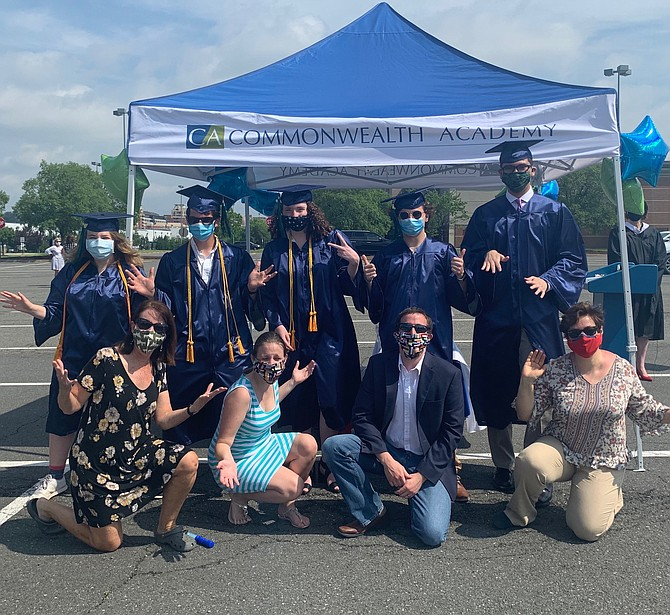 Dressed in caps and gowns, seniors Hazel Feldstein, Ewan O'Donnell, Lucy Souilliere, Max Leopold, and Mattias Camacho, together since 3rd grade, celebrate their graduation from Commonwealth Academy during a drive-in ceremony June 5 at Potomac Yard. In front are teachers Jane Furey, Rose-Marie Parker, Santiago Sere and Ksenya Litvak.