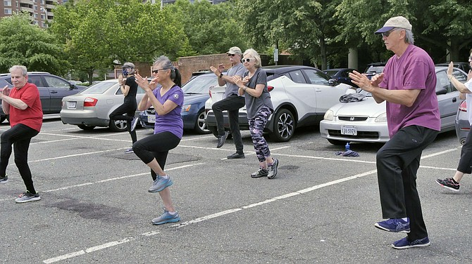 A YMCA Tai Chi class is held in the Central Library parking lot.