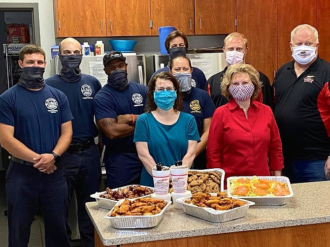 The Friendship Veterans Fire Engine Association delivers a meal from Foster's Grille to AFD headquarters June 5. Pictured in back, left to right, are Tyler Fredericks, Russel Thorne, Myron Dent, Erin Mustian, Scott Corder, Michael Catts and Bruce Catts. In front are Catherine Weinraub and Marion Moon.