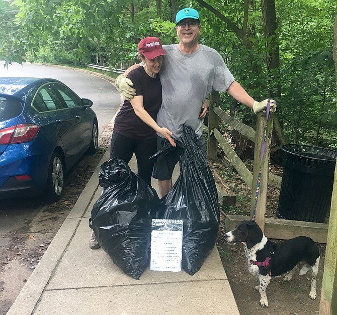 Karen Hannigan and Joe Schwartz, of Bluemont and Lyon Park neighborhoods, with their full garbage bags and their dog, Sadie, after a morning's work picking up trash.