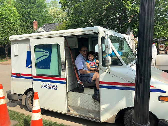 Jesus Collazos in his mail truck with his first granddaughter, Juliana Collazos.