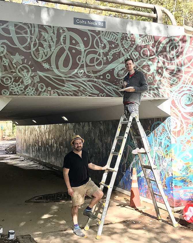 Artist Ben Volta talks with James Tafel Shuster as he paints panel edges to ensure color consistency in the massive Colts Neck Road underpass mural, a commissioned artwork in Reston. (File photo)