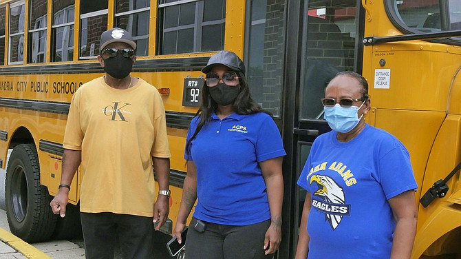 William Roos, Marquetta Lynch, and Zufan Endrais, repurposed school bus drivers, wait outside T.C. Williams for their buses to be loaded with Grab N' Go breakfasts and lunches for Alexandria school children.