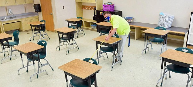 An FCPS employee prepares a classroom for In-Person Instruction with Social Distancing, one of two plans for academic year 2020-21.