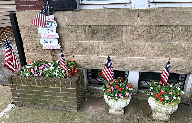 Flower pots adorned with American flags are part of a patriotic display at the Old Town home of Bernadette Troy, who is continuing the tradition of her late husband Pat Troy.