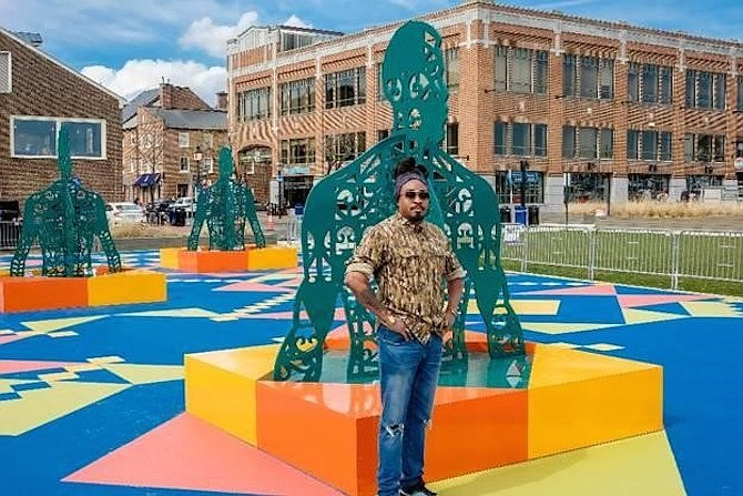 Artist Olalekan Jeyifous standing with Wrought, Knit, Labors, Legacies, a new public art exhibit at the Alexandria waterfront.