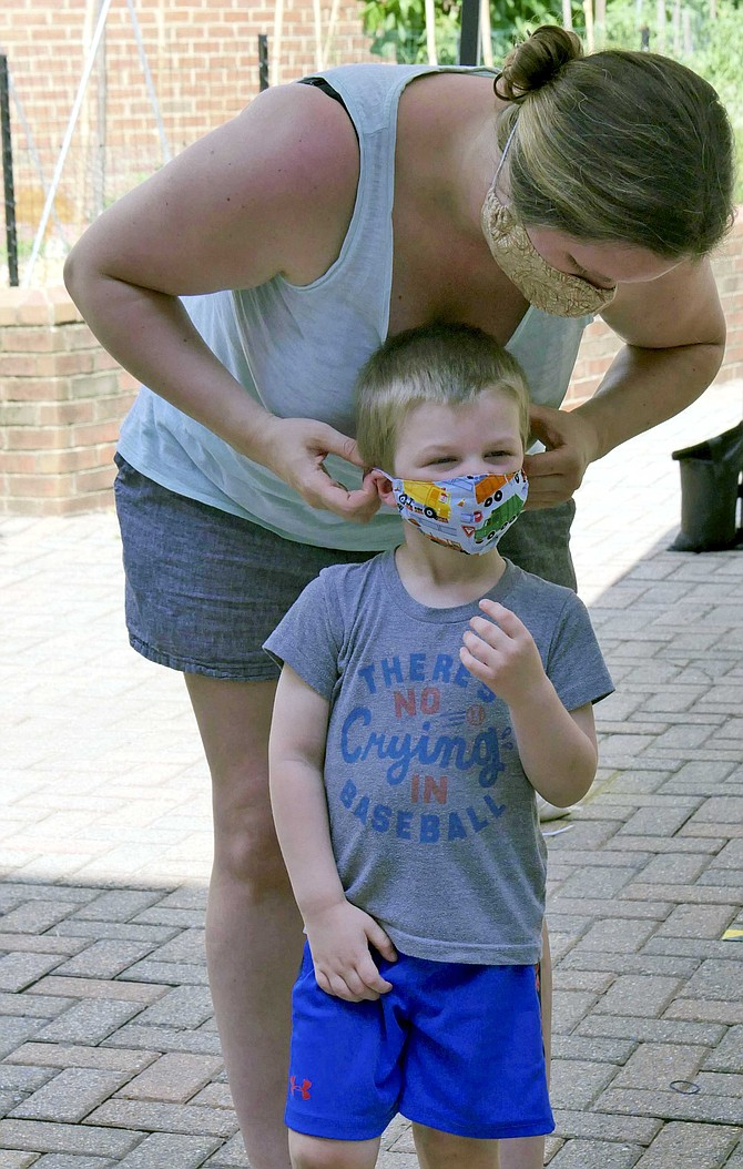 """Jennie Bruesewitz adjusts the mask of three-year-old, Henry Bruesewitz, while he waits under the newly-installed canopy at the Central Library for two books his mom has ordered through the """"holds pickup"""" initiative."""