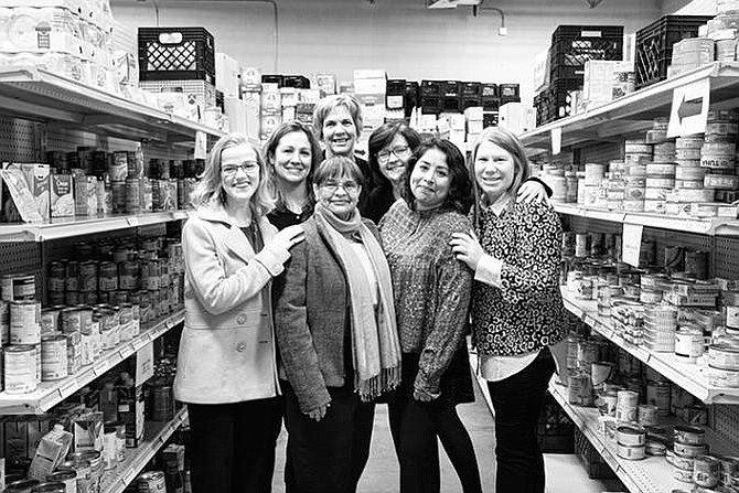 Harmonie Taddeo, Executive Director at Western Fairfax Christian Ministries (far right) and staff pause a moment in the organization's food pantry which serves clients at risk of hunger who reside in Oak Hill, Fairfax, Centreville, Clifton, Fairfax Station, Chantilly and Fair Oaks.  (File photo dated before COVID-19.)