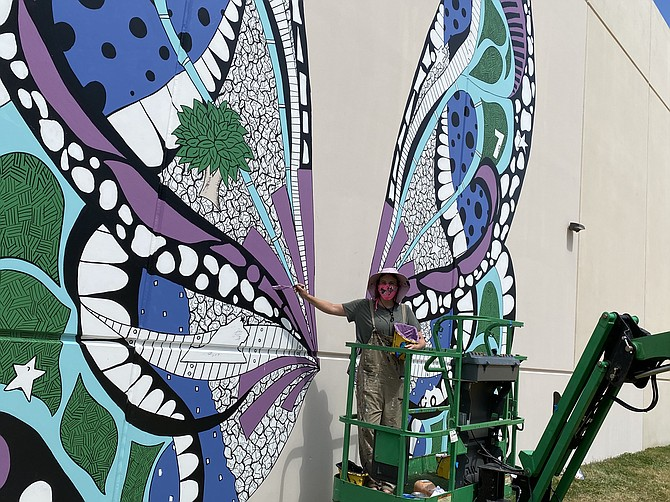 "Street artist Kelsey Montague paints ""Reston Wings Mural"" at International Tower at Reston Heights in Reston. Commissioned by American Real Estate Partners, the work is interactive."