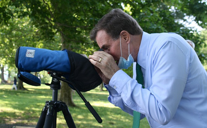 Sen. Mark Warner checks out an osprey off the shores of Belle Haven Park, visiting to talk about bipartisan support for the Great American Outdoors Act.