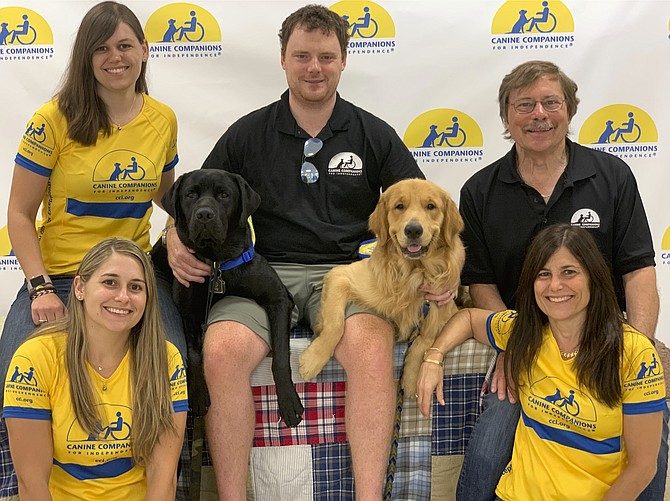 The Cheshire family of Great Falls with the dogs they raised, Buckner, the black Lab, and Zeno, the Golden Retriever. Top, from left: Nikki Cheshire, Raymond Junkins and Ben Cheshire. Bottom, from left: Tory Junkins and Jacqueline Cheshire.