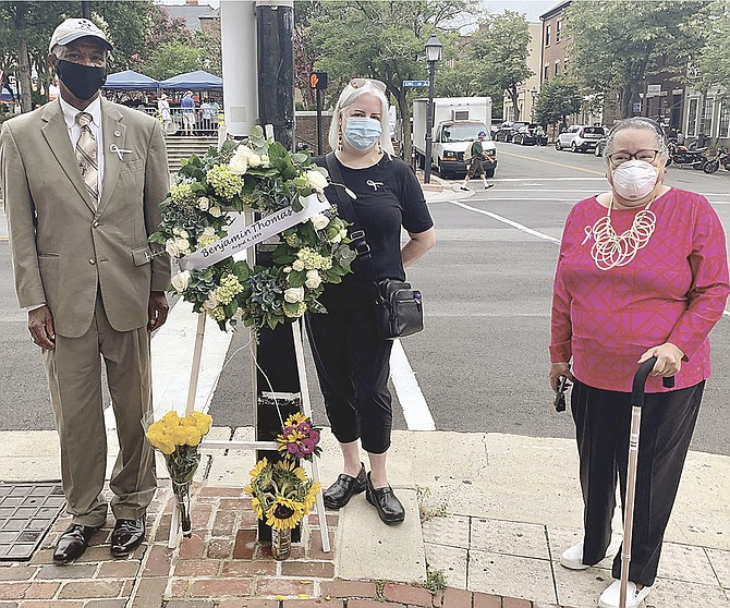 McArthur Myers, Maddie McCoy and Audrey Davis, director of the Alexandria Black History Museum, stand at the corner of King and Fairfax streets Aug. 8 to commemorate the 121st anniversary of the lynching of 16-year-old Benjamin Thomas in 1899.